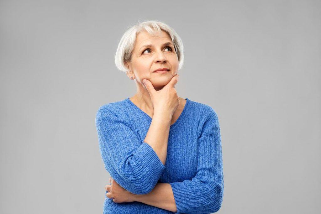 Frågande senior kvinna i blå tröja